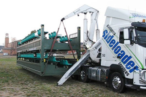 Sideloader lowers portable grandstand to the ground